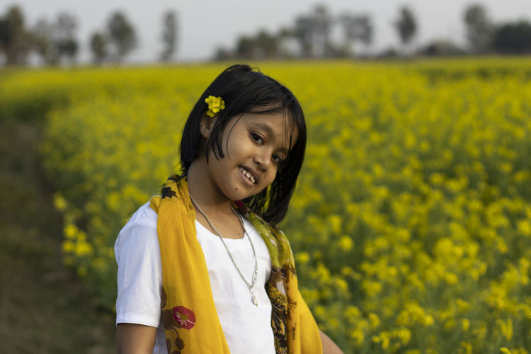 Portrait of a smiling young woman standing on field