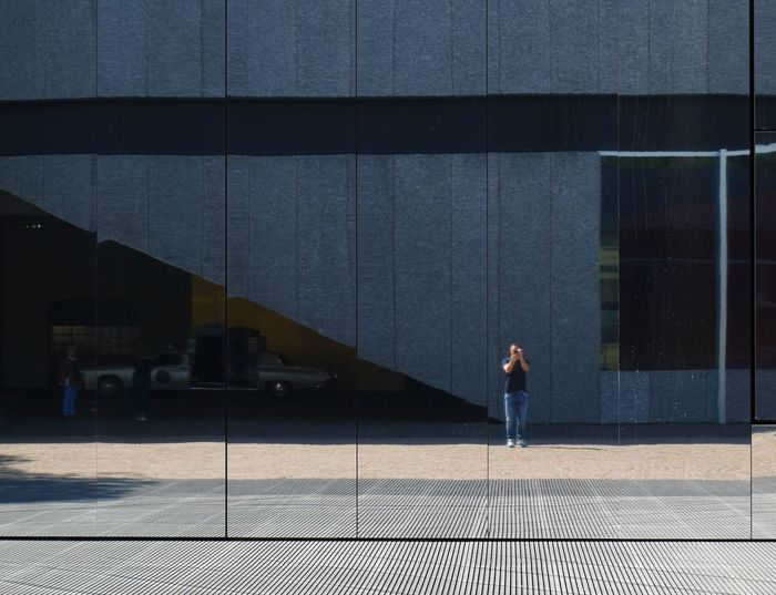 Man reflecting on glass building while standing on sidewalk in city