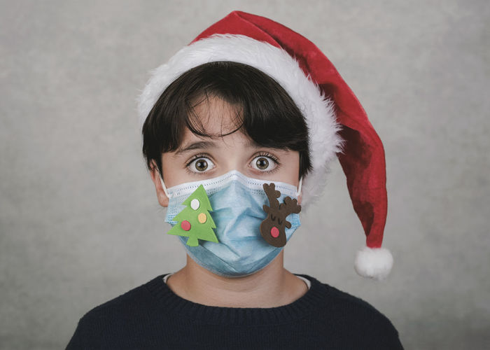 Portrait of boy wearing mask and santa hat standing against wall