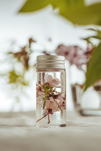 Close-up of essential oil and flowers on table
