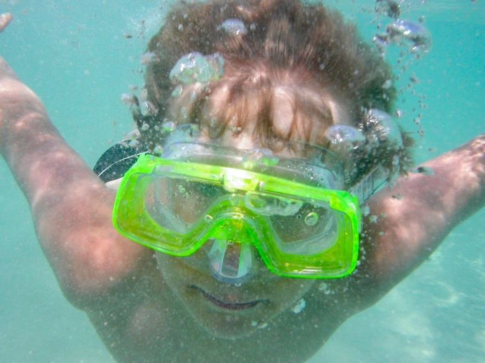 Young boy diving. One Person Bubble Leisure Activity Water Real People Lifestyles Close-up Sport Motion Swimming Goggles Underwater Headshot Swimming Front View Portrait Young Adult Shirtless Day Nature One Man Only Sea Dive Snorkeling Diving Mask Snorkel