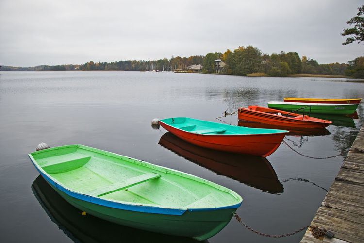 Old wooden boats near the beach of trakai gavle lake, lithuania. autumn and fall time.