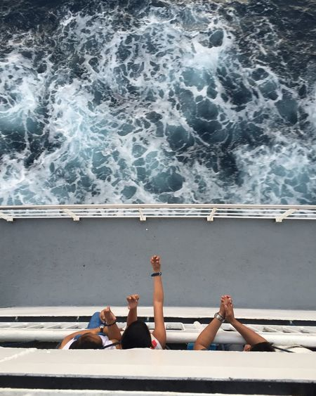 Directly Above Shot Of Friends On Ferry Sailing In Sea