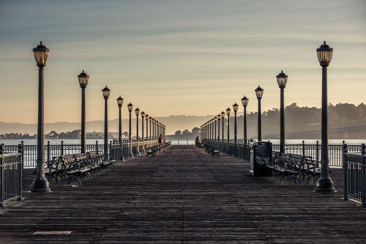 Walkway by railing against sky