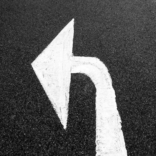 Turn left symbol painted in white on black road surface Arrow Asphalt Black And White Change Change Direction Direction Directly Above Ground Guidance High Angle View Information Left Outdoors Road Road Marking Sign Street Symbol Textured  The Way Forward Turn Left