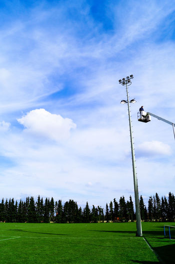 Low angle view of man on cherry picker by floodlight against sky