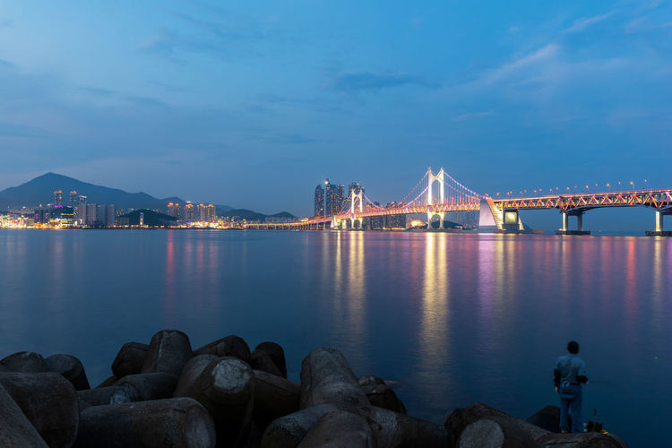 Illuminated bridge over sea against sky at dusk