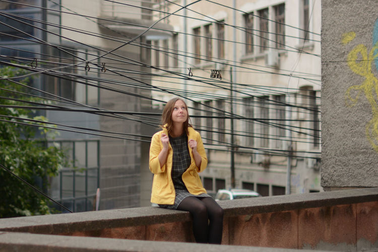 Mid Adult Woman Sitting On Railing Wall In City
