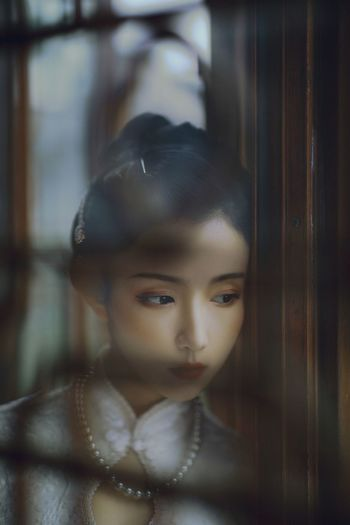 Portrait of a girl looking through window