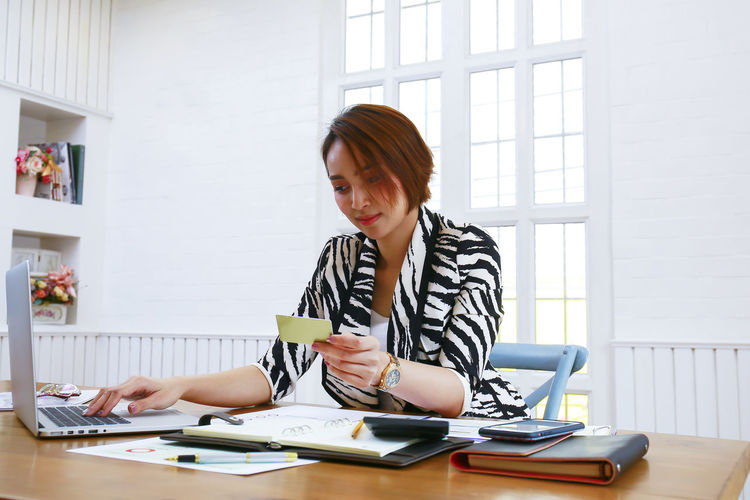 Businesswoman Using Credit Card And Laptop At Desk In Office