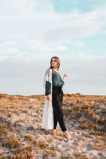 Fashionable woman standing on field against sky