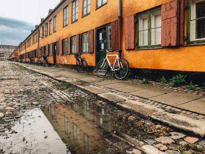 Bicycle parked by building in canal