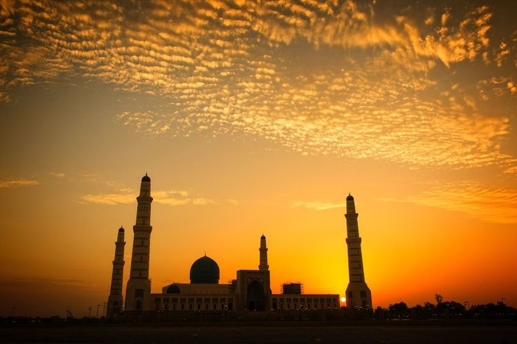 Low angle view of mosque against orange sky during sunset