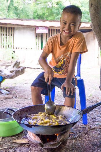 Portrait of boy preparing food while sitting on chair in yard