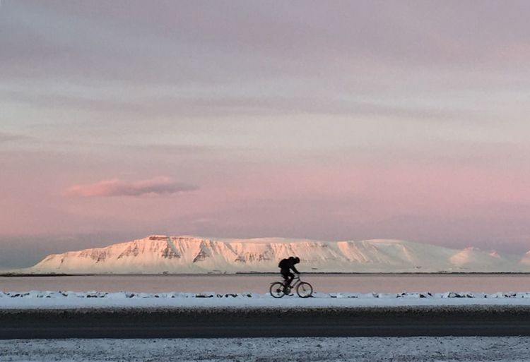 Man riding bicycle on snow field against sky during sunset