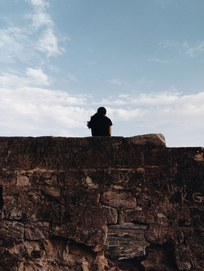 Rear view of man sitting on rock against sky
