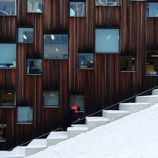 Person Climbing Steps Against Building During Winter