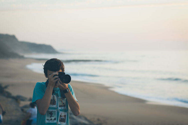 Man photographing with digital camera at beach during sunset