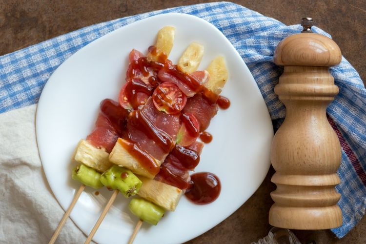 Directly Above Shot Of Food In Skewers On Plate With Pepper Bottle