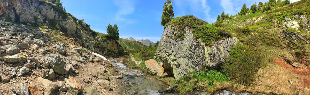 Panoramic view of rock formation amidst trees against sky