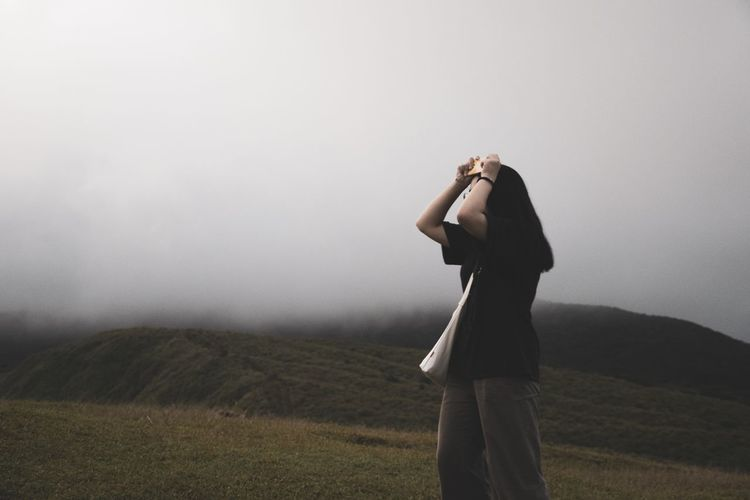 Woman standing on landscape during foggy weather