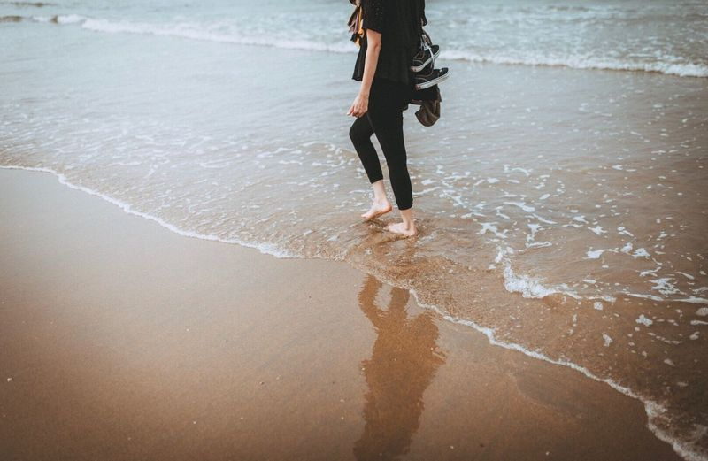 Low section of woman walking on beach