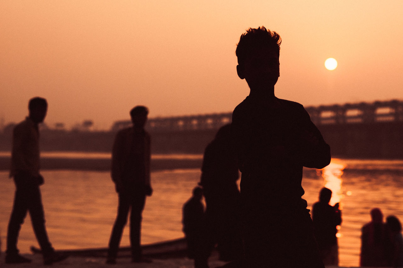 sunset, silhouette, sea, water, orange color, beach, real people, leisure activity, men, nature, vacations, lifestyles, togetherness, standing, outdoors, women, sky, beauty in nature, scenics, clear sky, day, people