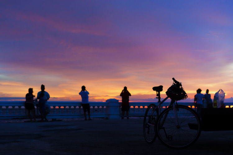 Evening Sky Background Twilight Silhouette The Great Outdoors - 2018 EyeEm Awards Beach Beauty In Nature Bicycle Cloud - Sky Group Of People Land Leisure Activity Lifestyles Men Nature Orange Color Outdoors People Real People Riding Sea Silhouette Sky Sunset Transportation Water Friend Cycling Horizon Over Water