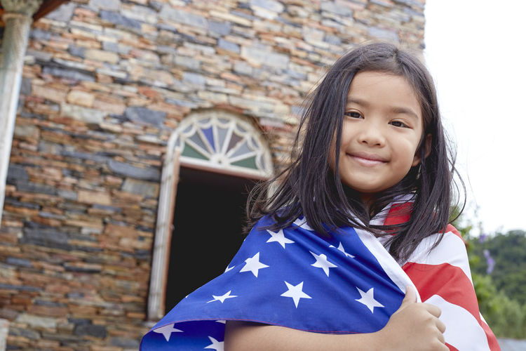 Portrait of smiling girl wearing american flag against building