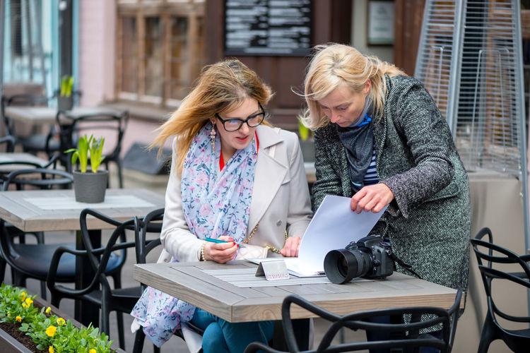 Females looking file at sidewalk cafe