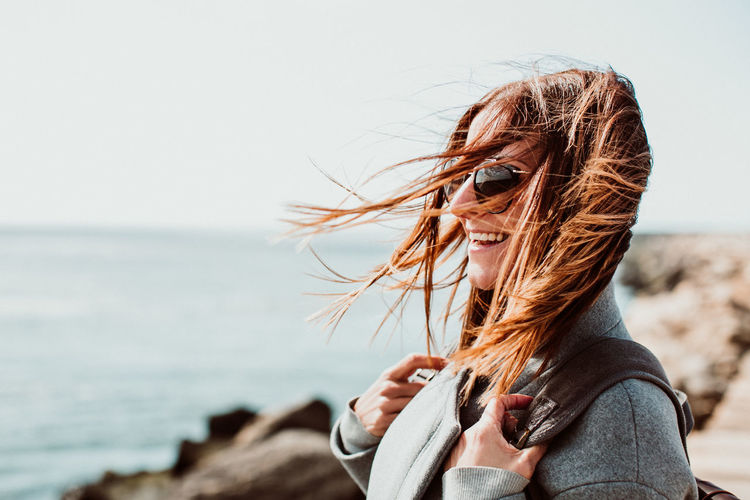 Side view of happy woman with tousled hair standing on pier over sea against clear sky