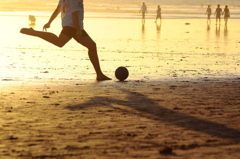 Low section of man playing soccer at beach during sunset