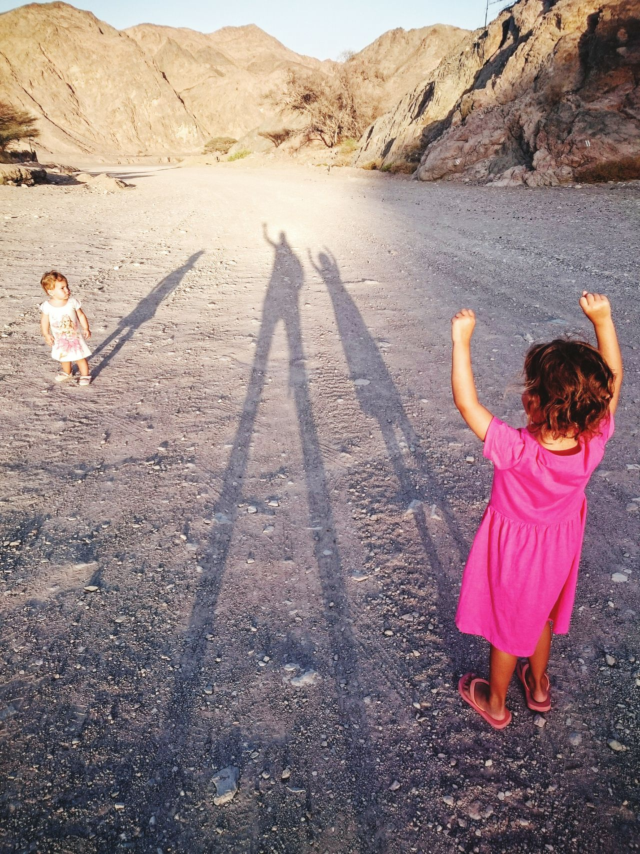 Shadow of family on arid landscape
