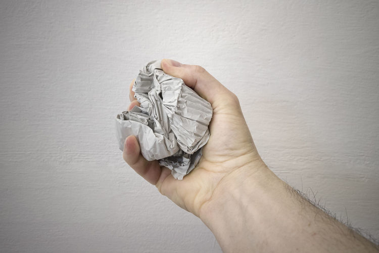 Close-up of hand holding paper against wall