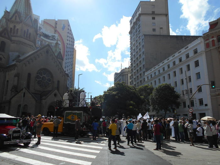 "A group of people participate in the Corpus Christi outdoor Mass and demonstration ""Pastoral do Povo da Rua"" held at the Santa Ifigênia church in downtown São Paulo on May 31, 2018. In Brazil, Corpus Christi is a Catholic celebration commemorating the Eucharist (the Eucharist is the symbolic presence of the Body of Christ in the consecrated host). The Corpus Christi holiday does not happen on the same day every year. This photo is a street scene in front of the Santa Ifigênia church. Corpus Christi Corpus Christi Holiday Igreja Santa Ifigênia Igreja De Santa Ifigênia May 31 May 31, 2018 Santa Ifigenia Viaduct Susan A. Case Sabir Unretouched Photography Belief Catholic Faith Catholic Religion Downtown São Paulo Large Group Of People Outdoor Mass Outdoor Congregation Reinforcement Religious Holiday Santa Ifigenia Street Photography Street Scene Sunny Day Togetherness Urban Photography Vintage Car"