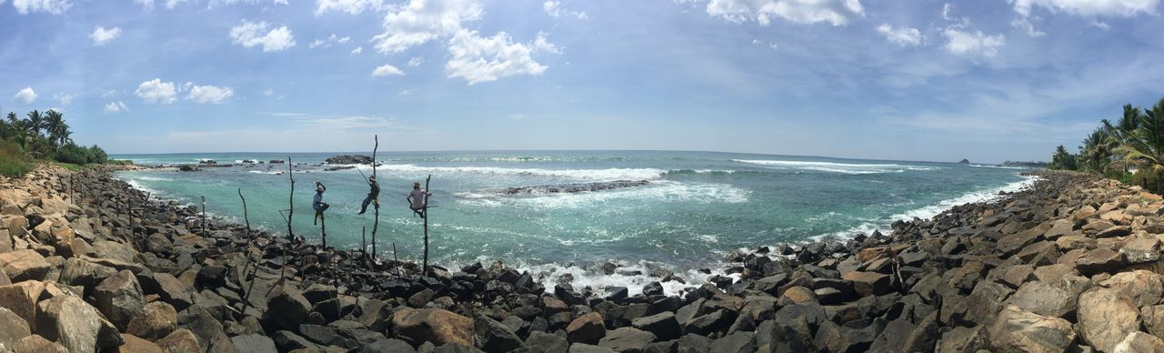 Panoramic view of sea with rocky shore against sky