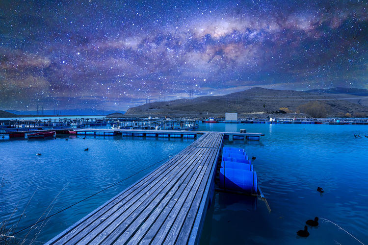 Atmosphere Cosmos Reflection Starlight Wood Astronomy Astrophotography Dock Galaxy Jetty Lake Milkyway Mountain Nature Nebula Outdoors Outerspace Sky Space Star Starry Startrails Universe Water