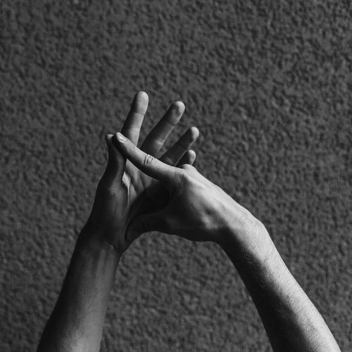 Cropped hands of man gesturing against wall