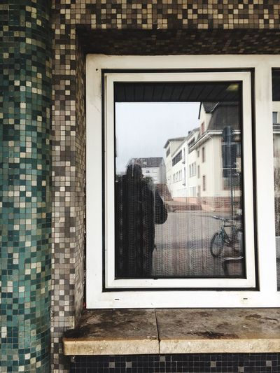 Reflection of man by buildings in window