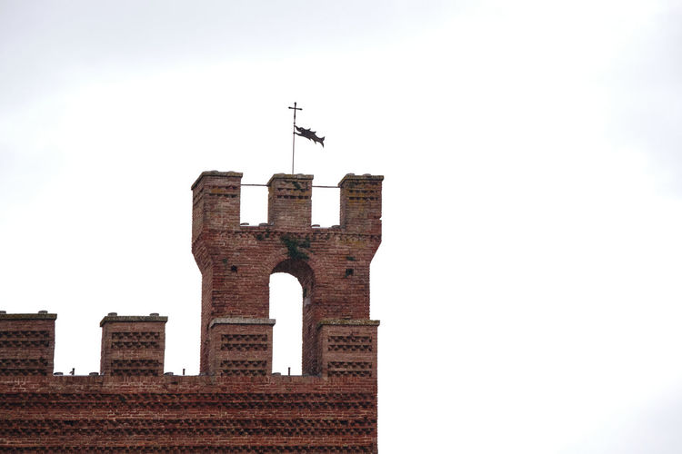 Low angle view of cross on building against clear sky
