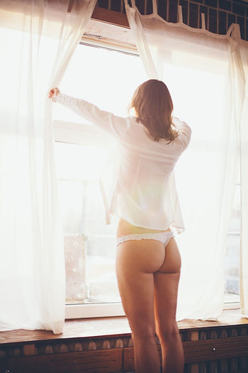 Rear view of seductive woman standing in front of window