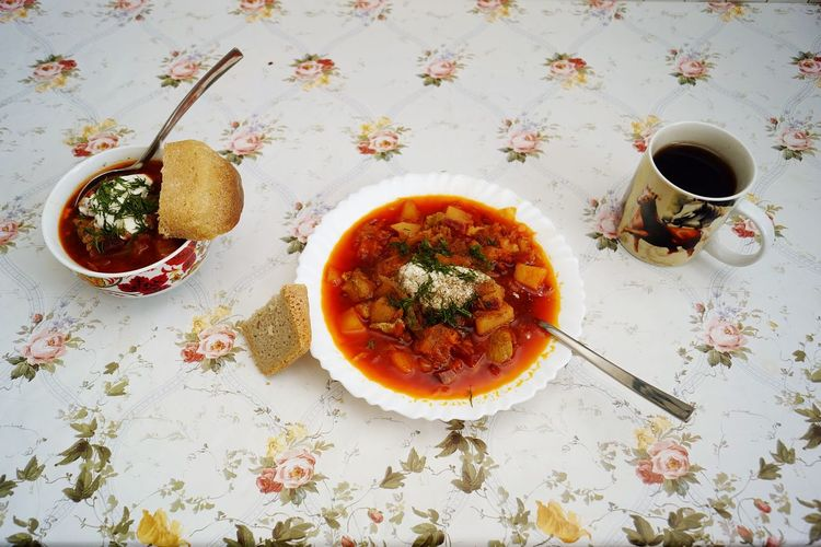 High angle view of borscht soup with bread and black tea on table