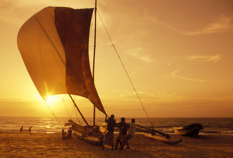 Rear View Of People Holding Boat Canvas At Beach During Sunset