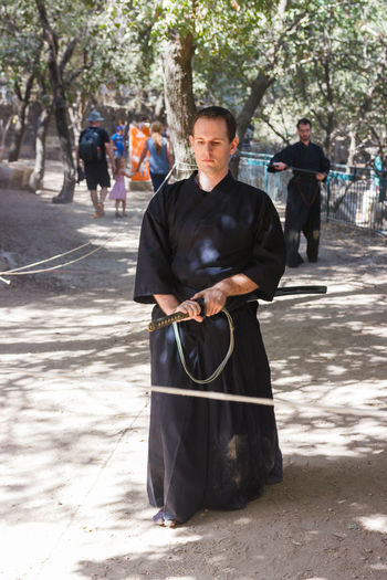 "Jerusalem, Israel, October 03, 2016: Member of the annual festival of ""Knights of Jerusalem"", dressed as a samurai shows exercise with sword in Jerusalem, Israel Ancient Annual Attraction Christian Citizen Decorations Dressed Event Famous Festival History Holy Israel Jerusalem Knight  Land Medieval Member Old Performance Performs Photographer Pose Sword Tradition"