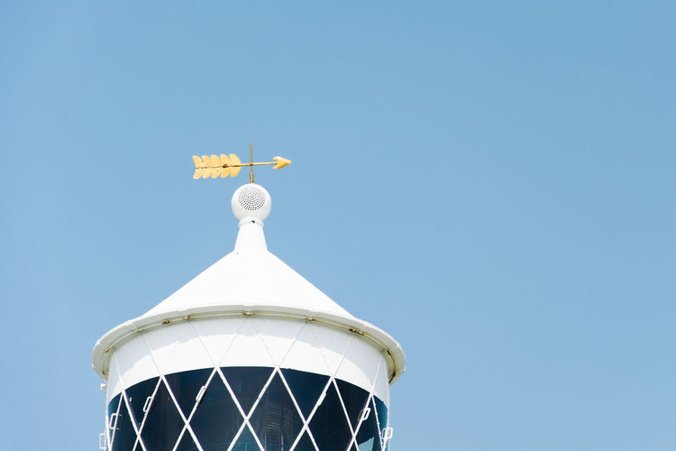 Low angle view of weather vane on tower