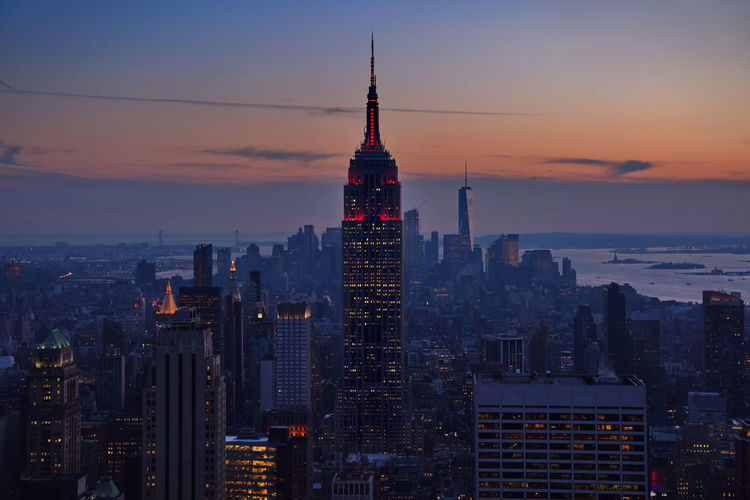 Illuminated empire state building in city against sky during sunset