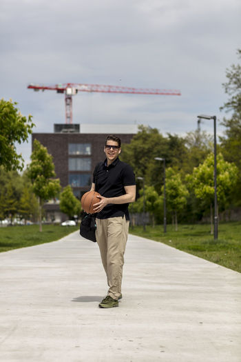 Close-up of mature man throwing basketball while standing outdoors