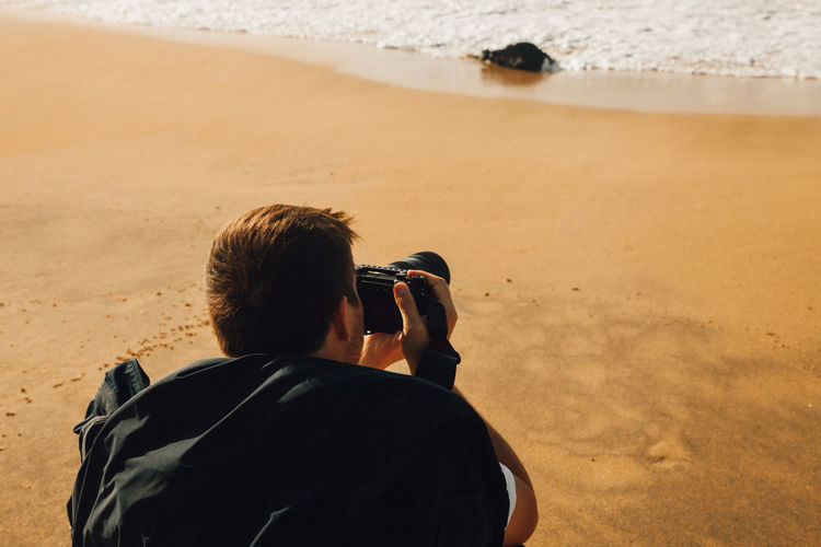 Rear view of man photographing on beach