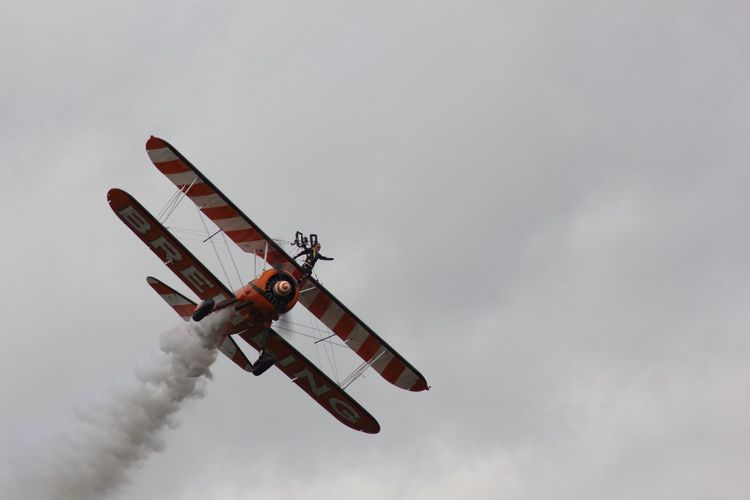 Low angle view of man performing stunt on biplane during airshow