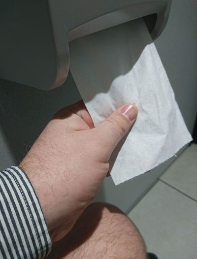 Cropped image of man removing toilet paper